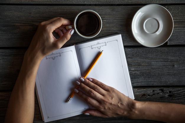 Mão feminina com uma xícara de café, fazendo anotações. funciona registros. o negócio