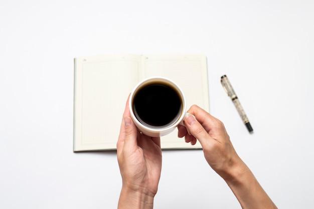 Mão feminina com uma xícara de café preto e um diário aberto com páginas limpas, uma caneta sobre um fundo claro. vista plana, vista superior