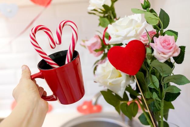 Mão feminina com uma xícara vermelha e flores. cartão de dia dos namorados, maquete