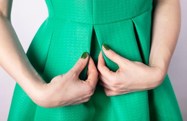 Mão feminina com unhas coloridas verdes em vestido verde. monocromático