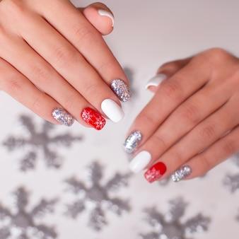 Mão feminina com unhas de manicure criativas, design de inverno