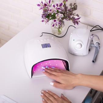 Mão feminina com unhas de manicure em lâmpada de polonês de gel em salão de beleza