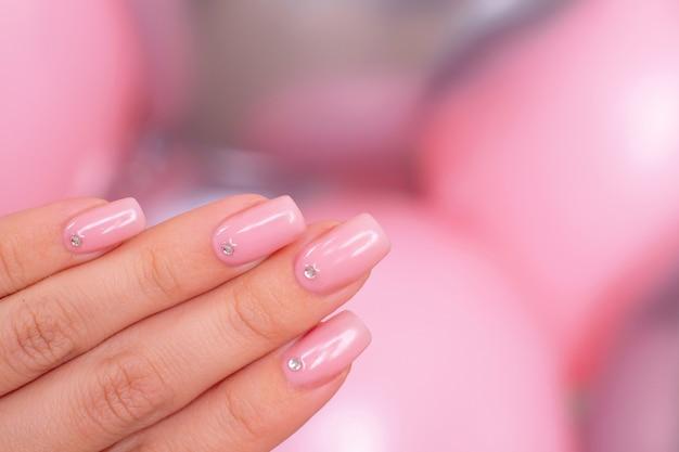 Mão feminina com unhas de manicure românticas
