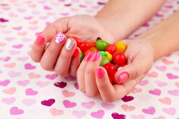 Mão feminina com unhas elegantes e coloridas segurando doces coloridos em uma superfície brilhante