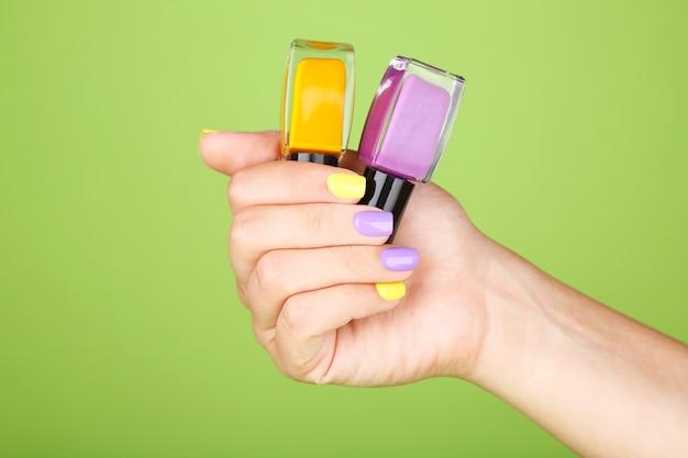 Mão feminina com unhas elegantes e coloridas segurando um frasco com esmalte
