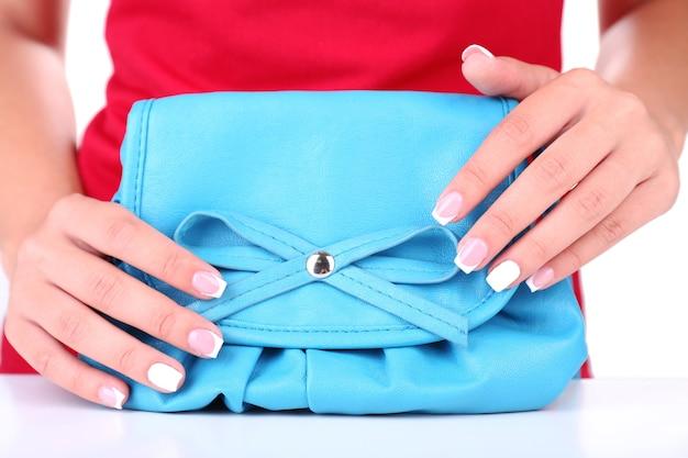 Mão feminina com unhas elegantes e coloridas segurando uma bolsa colorida isolada no branco