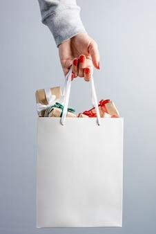 Mão feminina com unhas pintadas de vermelho segurando uma sacola de compras branca cheia de caixas de presente de natal
