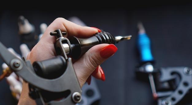 Mão feminina com unhas vermelhas, segurando a máquina de tatuagem. mão sem luvas - tatuagem de prática e treinamento. superfície escura