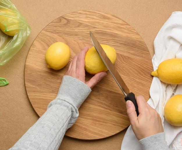 Mão feminina corta limões maduros amarelos em uma placa de madeira redonda, vista superior