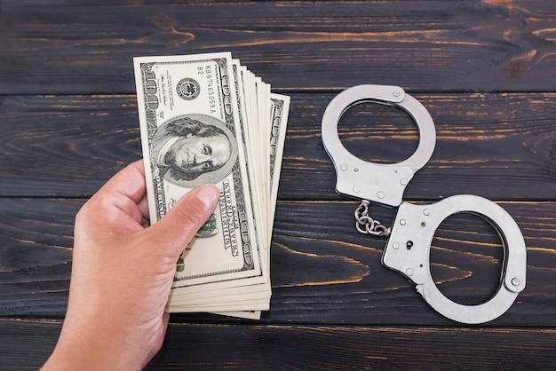 Mão feminina dá dinheiro no fundo de uma mesa de madeira e algemas. conceito de suborno e crime.