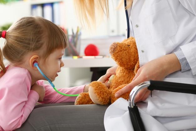 Mão feminina da menina espera estetoscópio ouvir