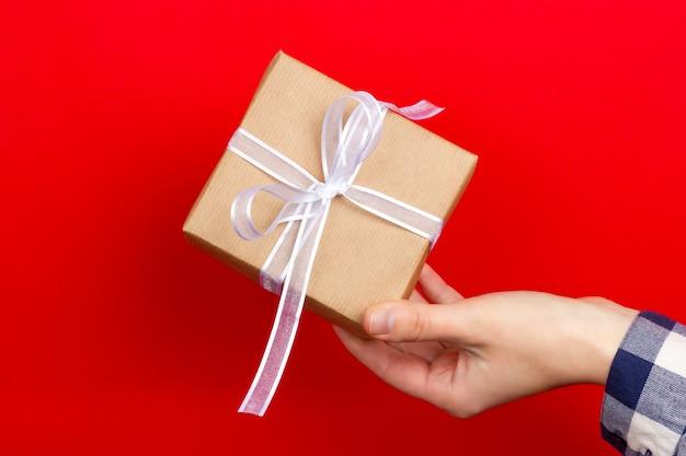 Mão feminina dá um presente embrulhado em papel artesanal