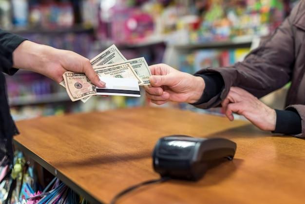 Mão feminina dando dólares e cartão ao caixa como forma de pagamento