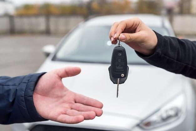 Mão feminina dando e mão masculina recebendo as chaves do carro