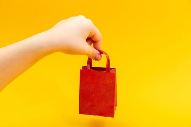 Mão feminina de adolescente segurando a sacola vermelha. conceito de dia dos namorados.