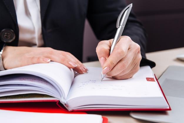 Mão feminina de escritório, escrevendo em um planejador diário vermelho
