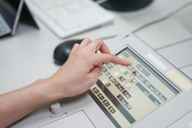Mão feminina de radiologista operando máquina de fluoroscopia enquanto caso paciente, conceito médico