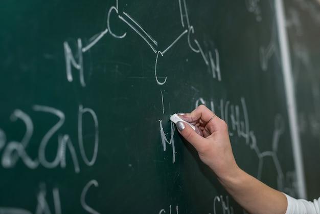 Mão feminina desenha equações químicas em um quadro negro. lição na escola