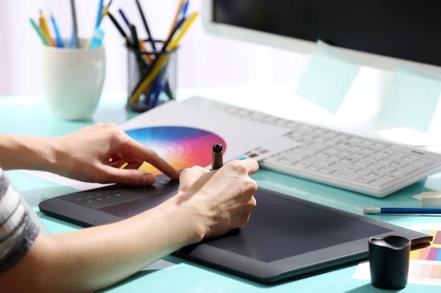 Mão feminina desenhando na mesa gráfica no escritório, close-up
