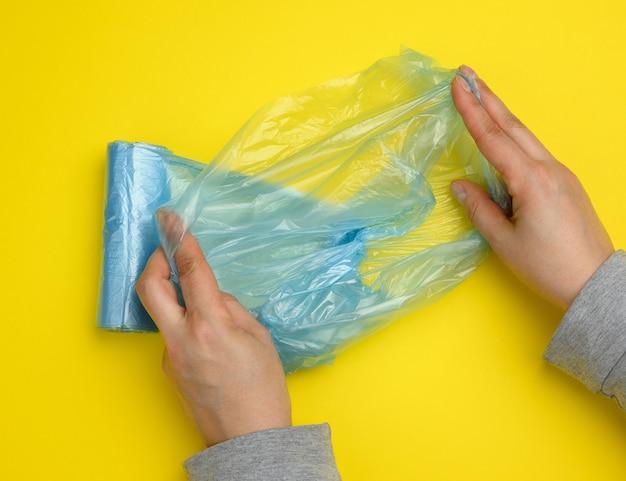 Mão feminina desenrola um saco plástico azul para lixo, fundo amarelo, vista de cima