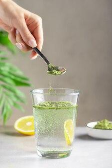 Mão feminina despejando pó de superalimento verde em um copo d'água