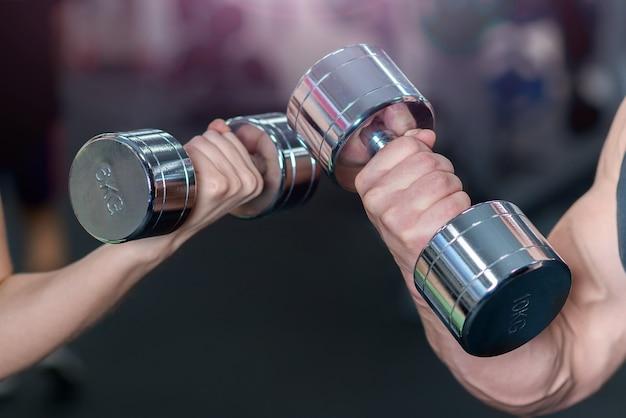 Mão feminina e masculina com halteres, close-up