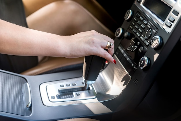 Mão feminina em close up da alavanca da transmissão automática