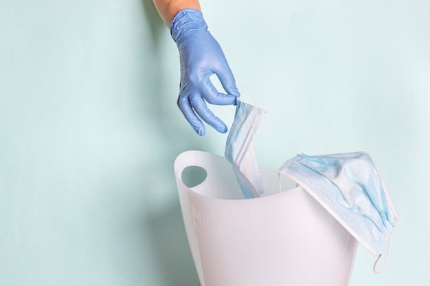 Mão feminina em luvas de borracha descartáveis lança máscara facial na lata de lixo