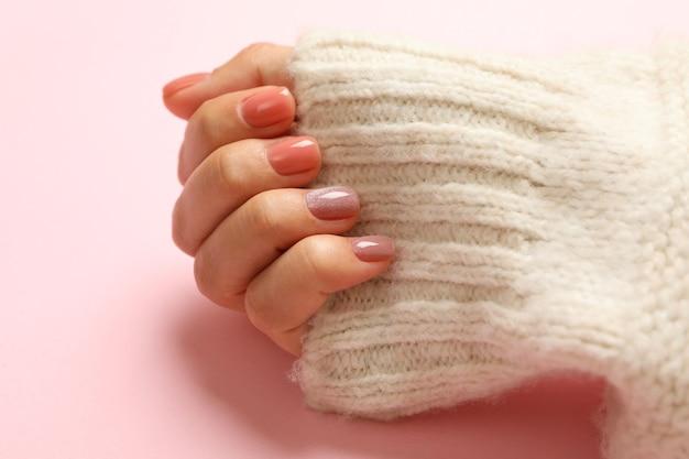 Mão feminina em suéter com unhas rosa isoladas