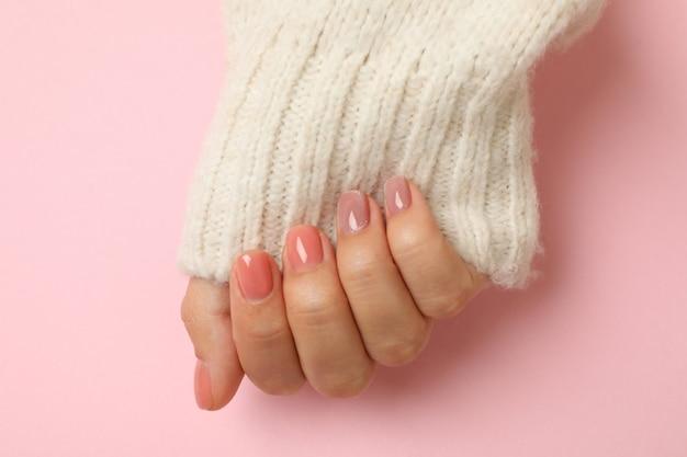 Mão feminina em suéter com unhas rosa