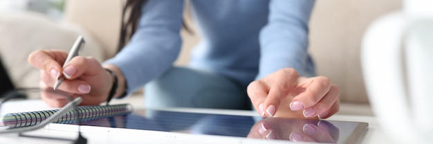 Mão feminina em tablet com segunda mão faz anotações com caneta em trabalho torcido de caderno e Foto Premium