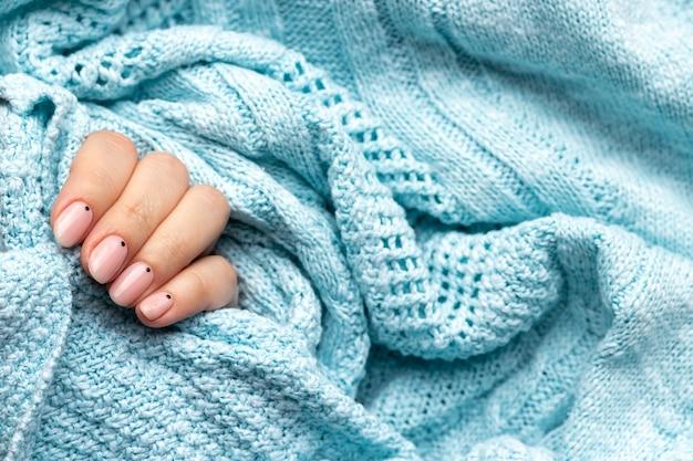 Mão feminina em tecido de malha azul com manicure da moda