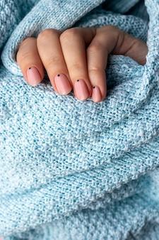 Mão feminina em tecido de suéter de malha azul com uma bela manicure na moda