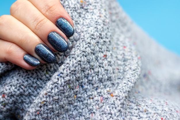 Mão feminina em tecido de suéter de malha cinza com bela manicure