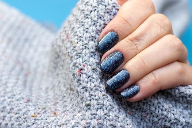 Mão feminina em tecido de suéter de malha cinza com unhas brilhantes azuis