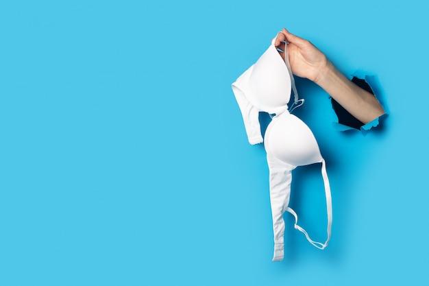 Mão feminina em um fundo azul segurando um sutiã branco novo