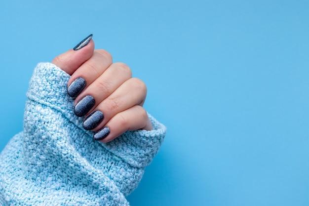 Mão feminina em um tecido de suéter de malha azul com uma bela manicure - unhas brilhantes de azul cinza escuro sobre fundo azul com espaço de cópia