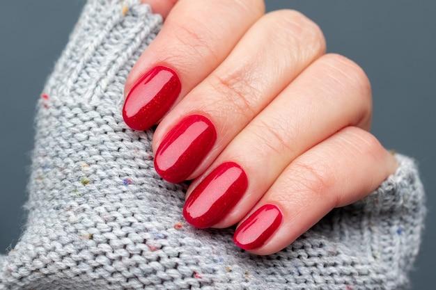 Mão feminina em um tecido de suéter de malha cinza com bela manicure - unhas vermelhas brilhantes. foco seletivo. vista de perto