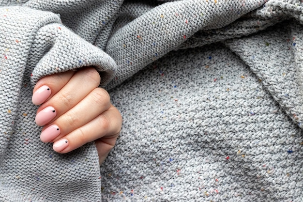 Mão feminina em um tecido de suéter de malha cinza com uma bela manicure na moda