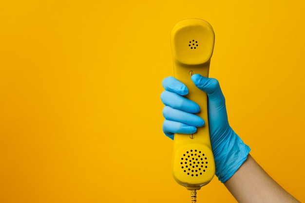 Mão feminina em uma luva médica segurando um alto-falante amarelo