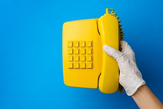 Mão feminina em uma luva médica segurando um telefone fixo amarelo