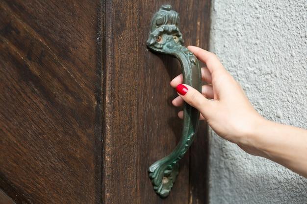 Mão feminina empurrando a maçaneta da porta. espaço vazio