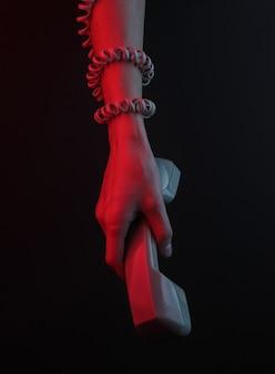 Mão feminina enrolada em um cabo segura um receptor de telefone em um fundo preto com uma luz neon vermelha
