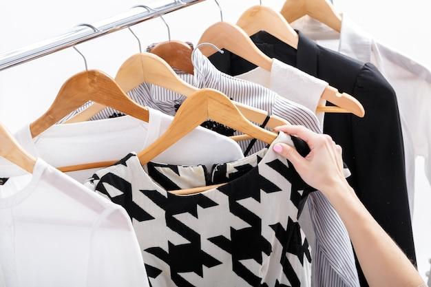 Mão feminina escolhe novas roupas da moda em cabides de madeira na prateleira em fundo branco, closeup. conceito de compras