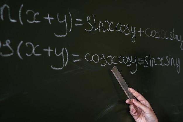 Mão feminina escrevendo fórmulas matemáticas no quadro, close-up