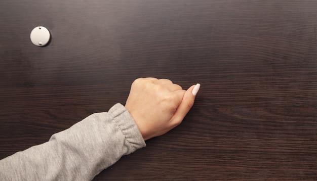 Mão feminina está batendo na porta