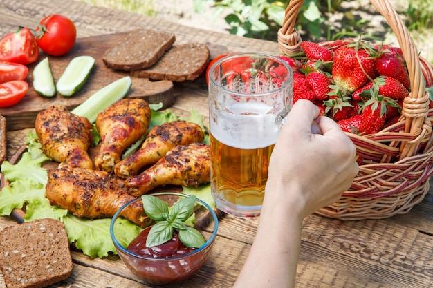 Mão feminina está segurando a caneca de vidro de cerveja com pernas de frango grelhado e tomate, pepino, dread preto, cesta de vime com morangos no fundo. foco seletivo na caneca