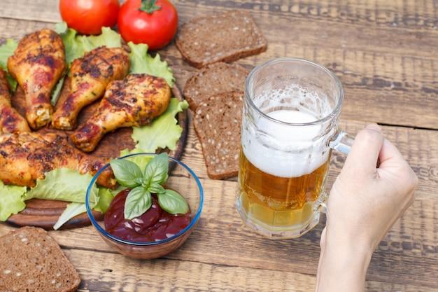 Mão feminina está segurando uma caneca de vidro de cerveja com pernas de frango grelhado e molho de tomate em uma tigela de vidro decorada com manjericão verde, tomate fresco e pão preto no fundo. foco seletivo na caneca