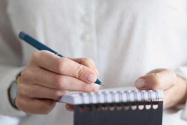 Mão feminina fazendo anotações em close do caderno