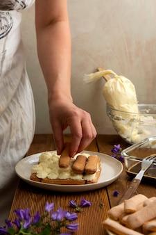 Mão feminina fazendo bolo tiramisu com biscoitos de esponja de dedo. passo a passo receita de sobremesa caseira de café